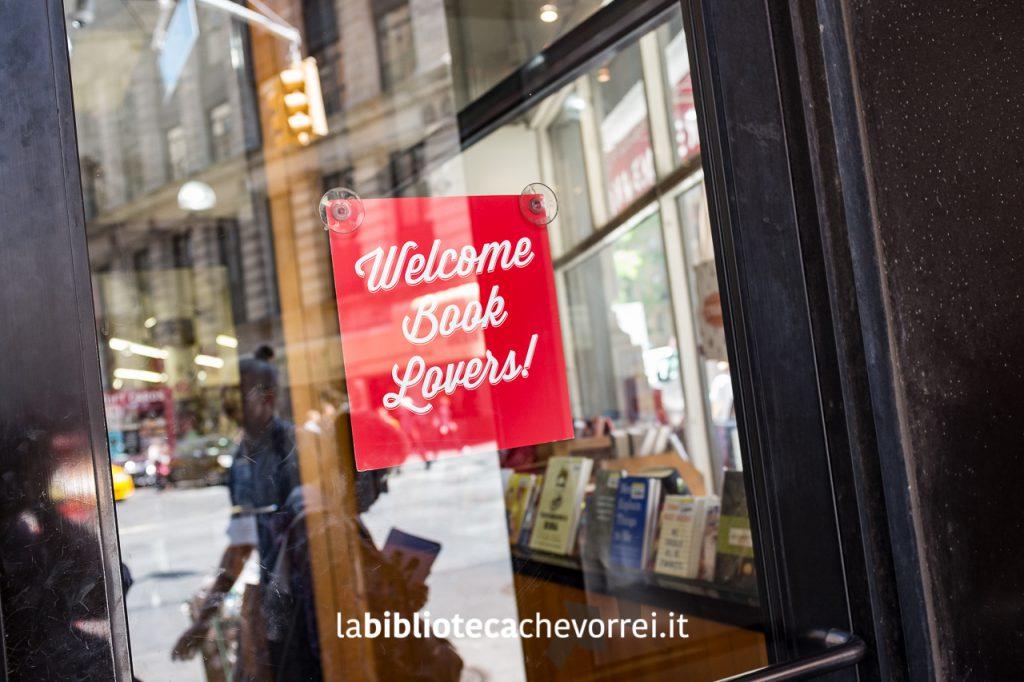 """Ingresso del negozio. Cartello con scritto """"Benvenuti amanti dei libri""""."""