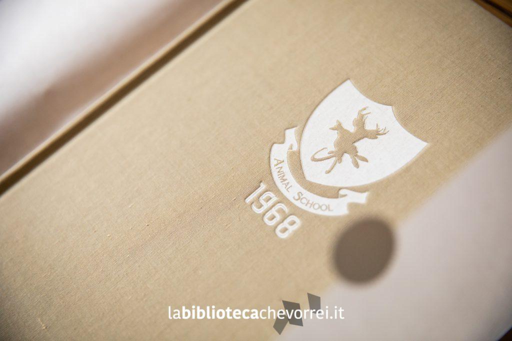 Dettaglio della copertina del libro The Animal School Yearbook con stemma stampato a pressione e vernice bianca.