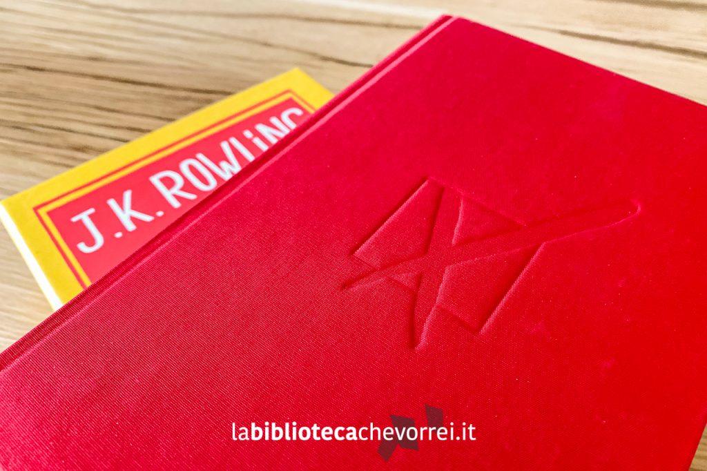 """Copertina dell'edizione speciale de """"Il Seggio Vacante"""" di J.K. Rowling in tela rossa e con il logo inciso."""