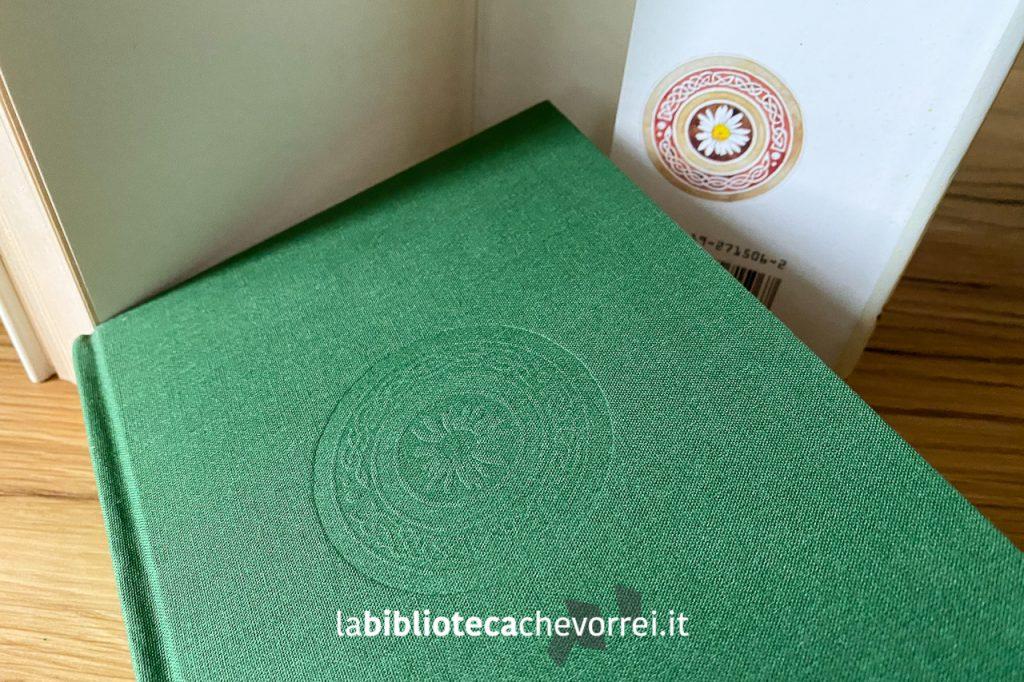 """La copertina dell'edizione italiana de """"La pietra del vecchio pescatore"""" con uno stemma impresso sulla tela di color verde."""